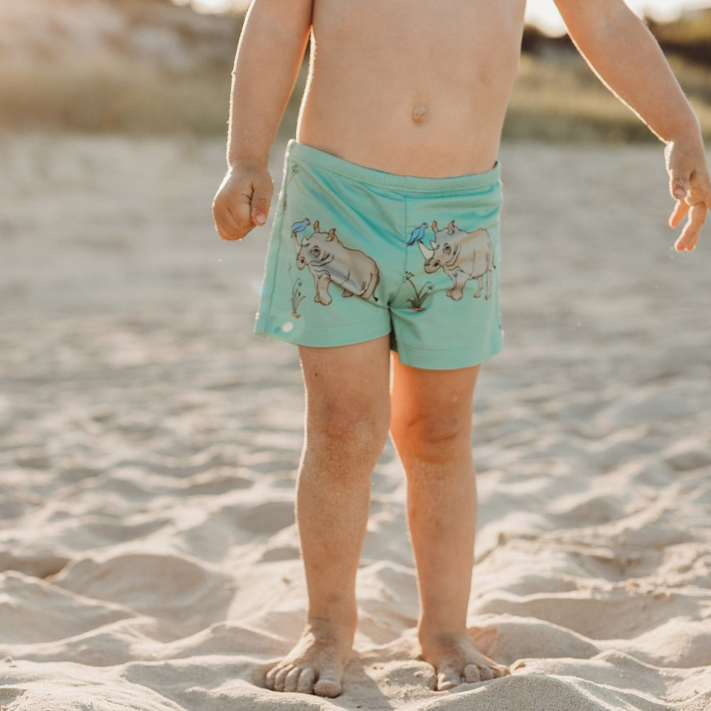 Closeup of toddler wearing swimmer shorts in a biscay bay blue featuring rhinos and tick birds