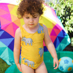 Toddler wearing one piece swimmers in bright yellow featuring rhinos in a repeat pattern.
