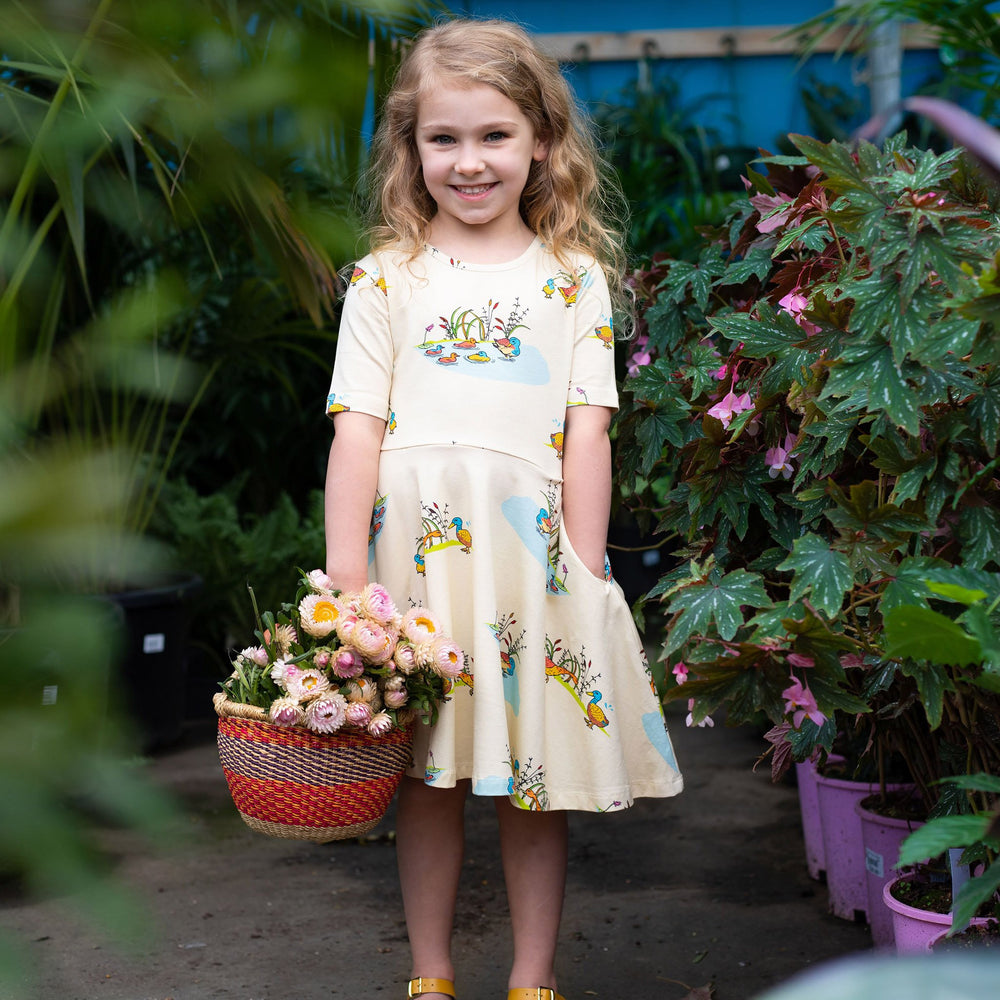 Girl wearing cream twirling dress that is printed with a Puckle Duck family illustration in a repeat pattern.  She is holding a basket of flowers and has her left hand in her dress pocket