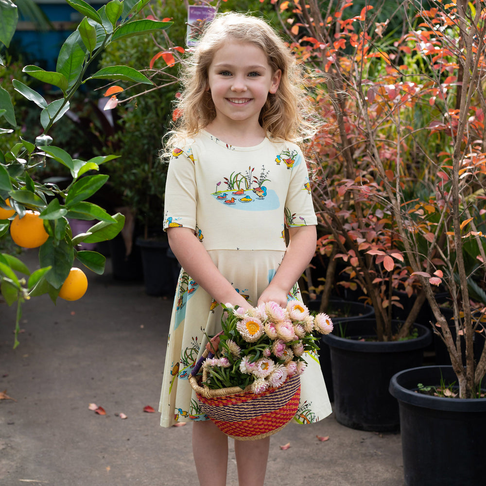 Young blonde girl holding basket of flowers.  She is wearing a short sleeved twirling dress with a duck family print in a repeat pattern.  The dress is a cream colour.