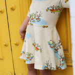 Close up of short sleeved knee length cream children's dress with Puckle Duck family illustrations in a repeat pattern.