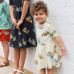 Smiling toddler wearing a cream twirling dress with a duck family print.  In the background is an older girl wearing a dark grey Caron coloured twirling dress featuring meerkats.