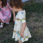 Toddler with curly hair wearing a cream duck dress with short sleeves.