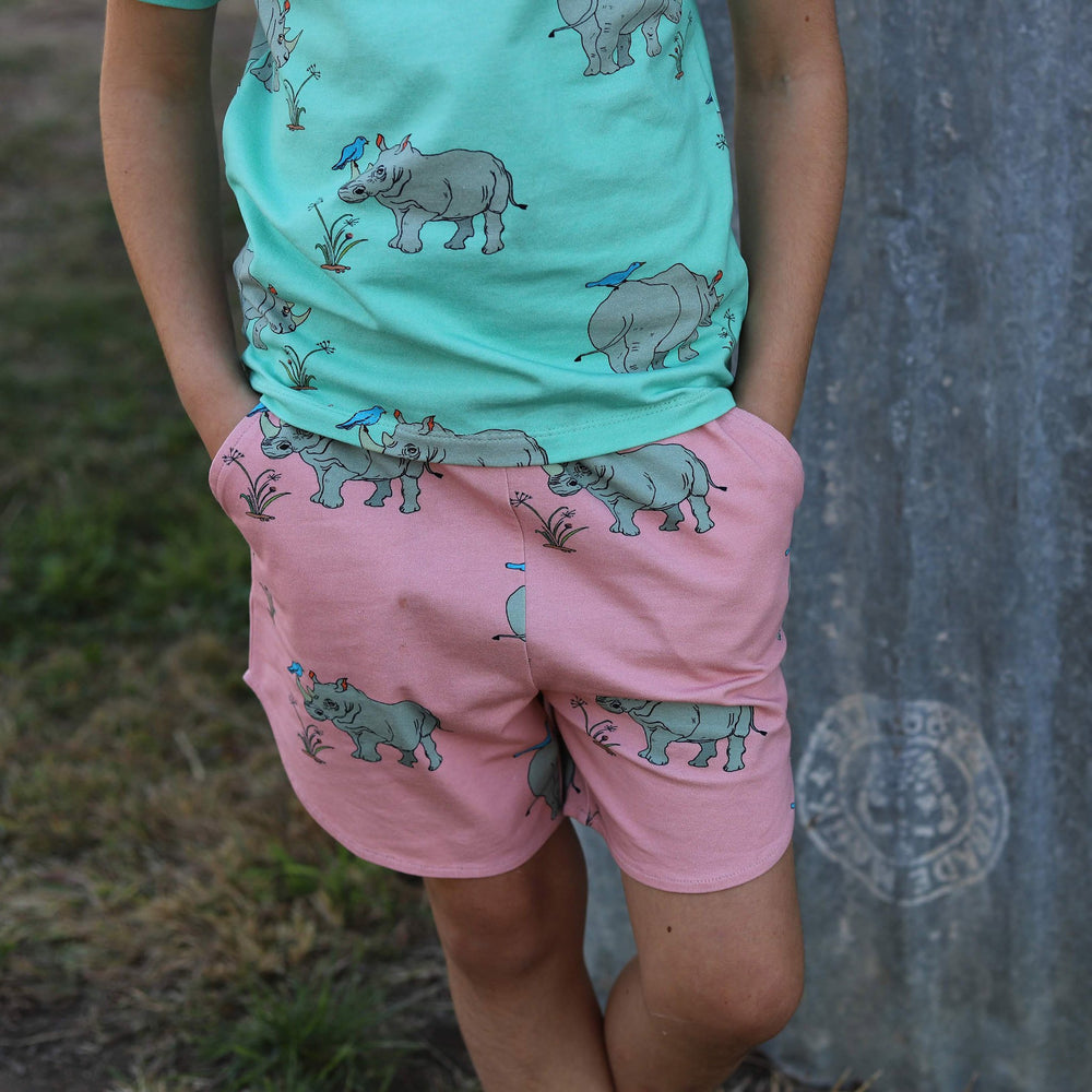 Close up of dusty pink coloured girls scalloped shorts with pockets.  Shorts feature a rhinoceros print in a repeat pattern.  Model has her hands in her pockets and is also wearing a matching biscay bay coloured matching tee in the same rhino print