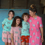 Family wearing matching scandi style clothing.  All clothing features a hand-drawn illustration of a rhino and tick bird.  Each item is on a different colour fabric base.  Blue short sleeved rhino tee and matching dusty pink rhino shorts.  Dusty pink girls rhino dress. Unisex blue rhino tshirt with matching red rhino shorts.  Bright pink Mumma scandi animal print dress with rhinos and tick birds.