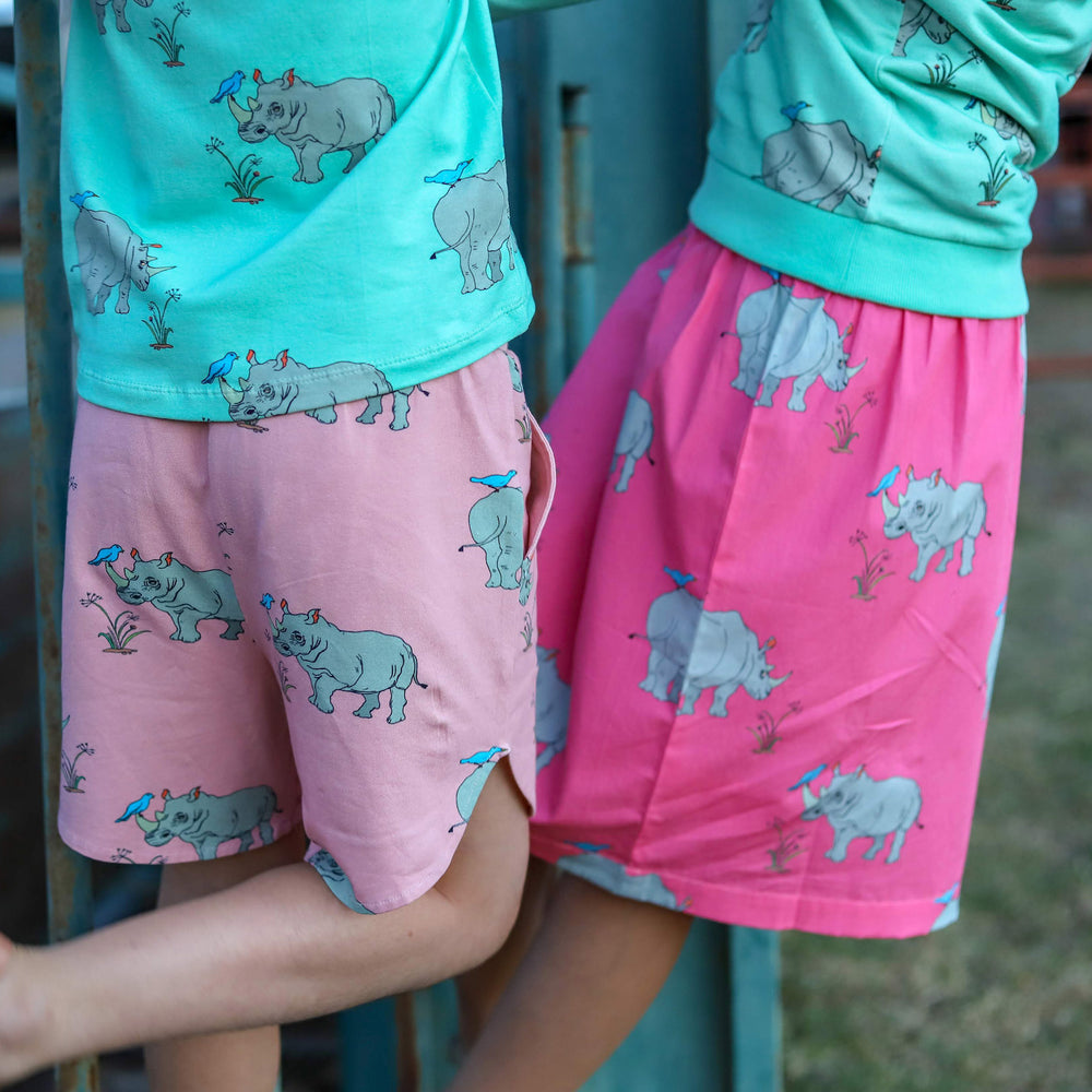 Close up of two kids wearing matching outfits.  Matching rhino tee in blue paired with dusty pink rhino shorts with pockets.  Blue rhino jumper with matching bright pink girls rhino skirt.