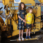 Unisex matching meerkat clothes by Oomph and Floss.  Girl wears meerkat twirling dress in carbon, boy wears yellow meerkat jumper and matching meerkat shorts.