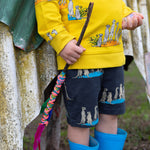 Toddler wearing matching meerkat clothing.  Grey meerkat shorts with pockets and drawstring waist and matching yellow meerkat jumper