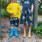 Siblings wearing matching scandi style clothing featuring meerkats.  Oomph and Floss meerkat dress on carbon grey.  Oomph and Floss meerkat jumper of yellow.  Oomph and Floss shorts with meerkats