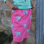 Girl wearing a organic cotton skirt in a vibrant pink with hand drawn illustrations of a rhino with a tick bird in a repeat pattern.  she is wearing a matching jumper in the same print on a bright biscay bay blue.