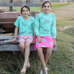 Two girls sitting on a wooden truck back wearing matching outfits.  The girl on the left wears short sleeved rhino tshirt in biscay bay blue and scalloped drawstring shorts with pockets in a dusty pink with the same rhino print.  The girl on the right wears a jumper from the same rhino print as the short sleeve tee and wears a matching brighter pink knee length rhino skirt