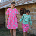 Mother and daughter holding hands wearing matching scandi-style colourful clothing for Mumma and daughter.  Mums dress is a bright pink rhino faric, the daughters skirt is from the same pink rhino fabric.  The daughter wears a lightweight jumper from the same rhino material but on a vibrant Biscay bay blue base.