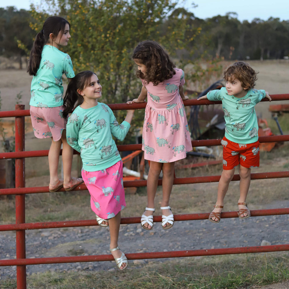 4 kids playing on a red metal fence wearing matching rhino outfits in a variety of colours.  Blue short sleeved rhino tee with matching dusty pink rhino shorts.  blue rhino jumper with matching pink rhino skirt.  Dusty pink rhino dress.  Red drawstring shorts with pockets in rhino print.