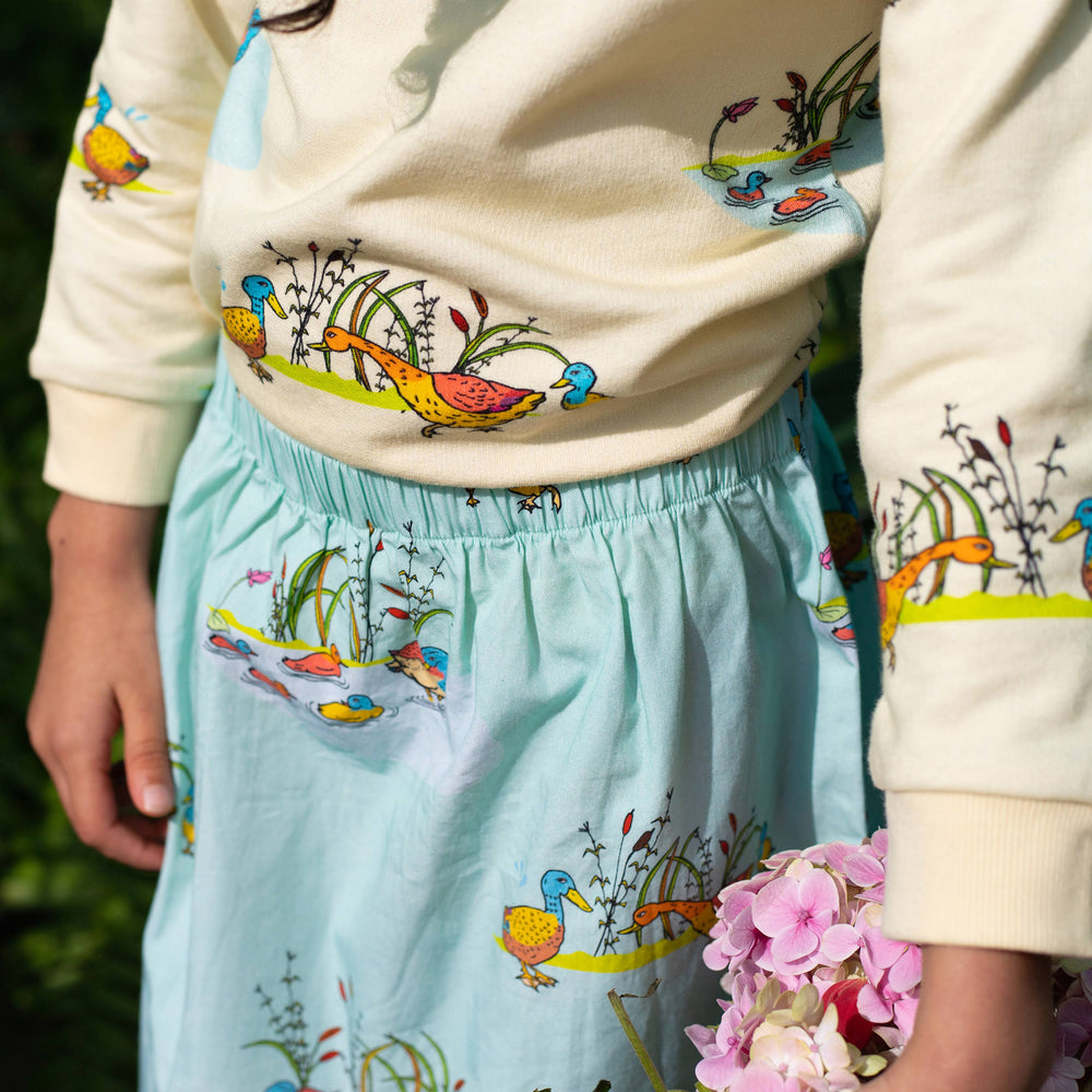 Close up of elastic waist band skirt.  Skirt is mint with ducks on it.  Girl wears a cream coloured jumper in the same matching duck print.