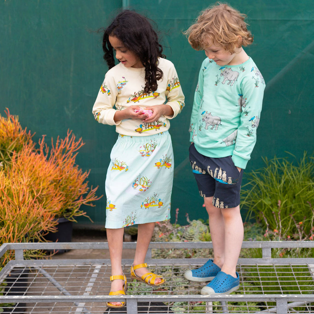 Girl wearing duck print skirt and matching kids unisex duck print jumper boy wearing kids unisex rhino print jumper and kids unisex meerkat print shorts,