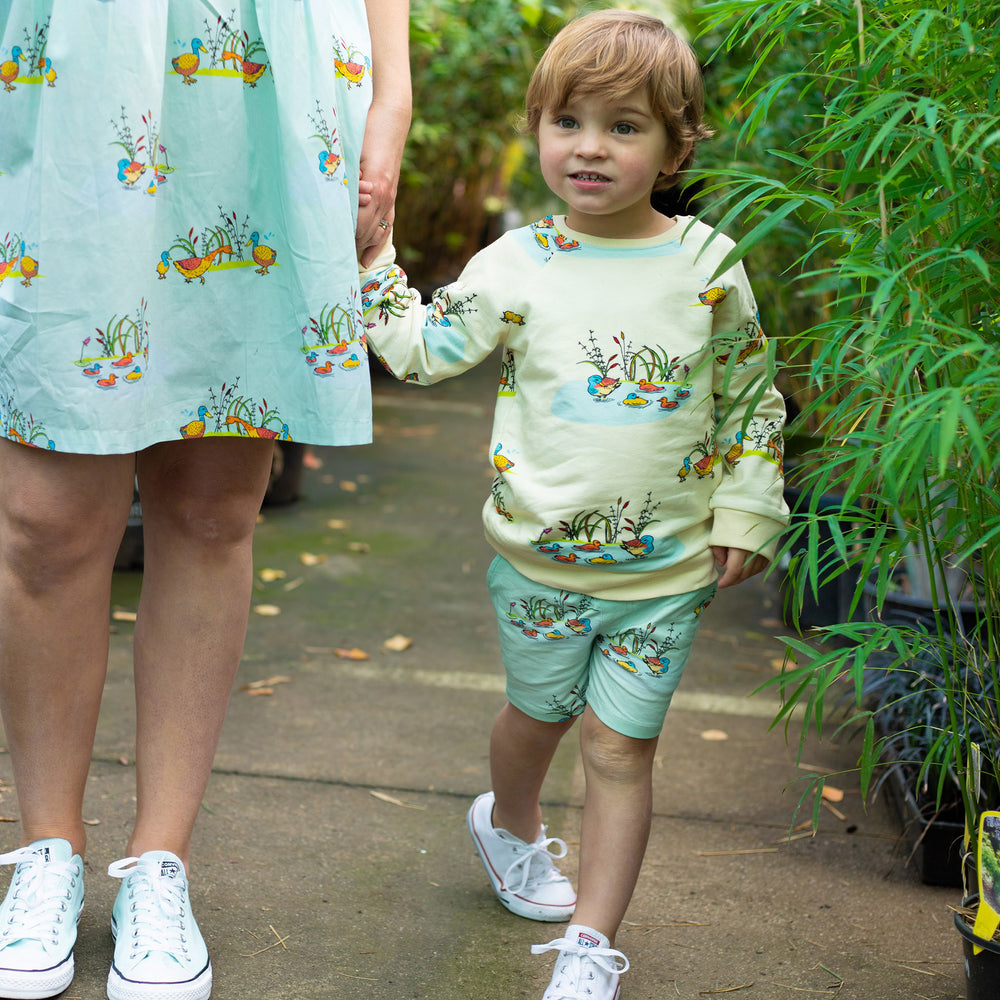 Mum and son wearing matching scandi-style clothes.  Mum wears adult duck print dress and son wears duck print shorts and matching duck print jumper.