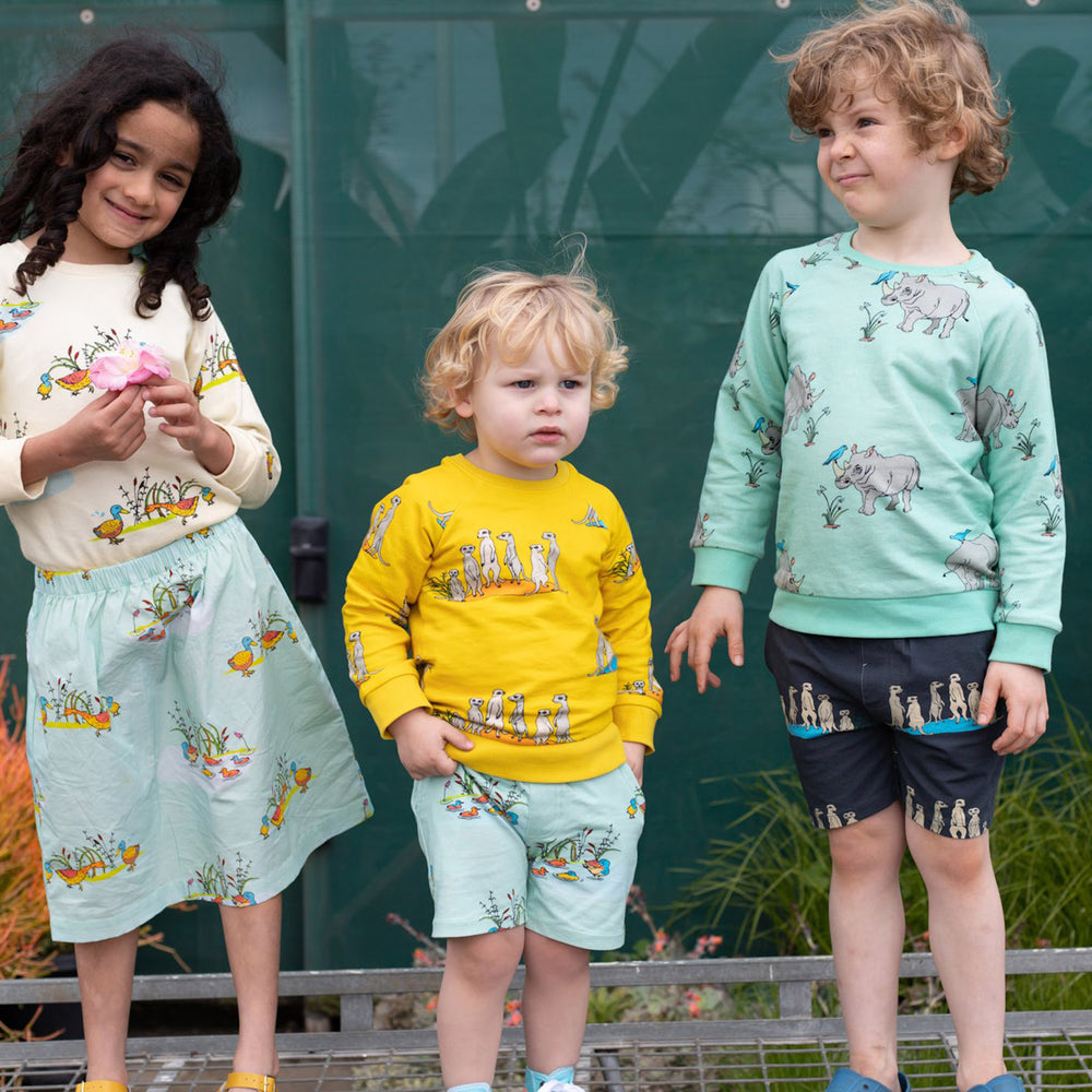 3 kids wearing matching scandi style clothing.  Girl on left wears cream duck jumper with matching mint duck skirt.  Boy in the middle wears yellow rhino jumper and duck print shorts.  Boy on right wears blue rhino jumper and grey meerkat shorts with pockets.