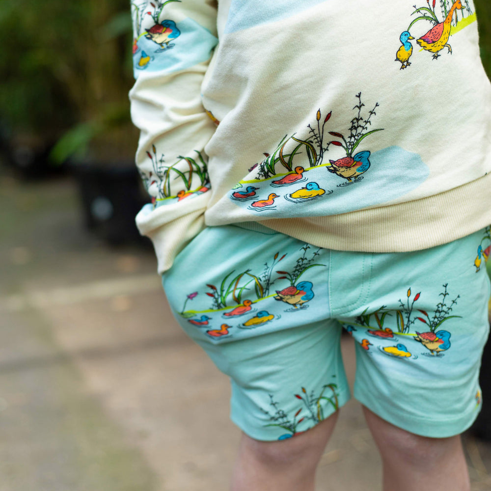 Child wearing shorts with pockets featuring Puckle Duck print in a repeat pattern.  Child has their hand in their pocket.  Child is wearing a cream jumper in matching duck print.