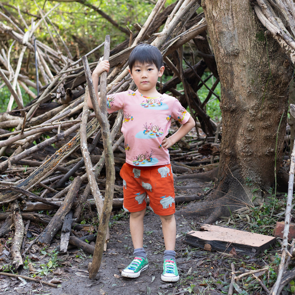 Young boy standing holding a large stick.  He is wearing tigerlily red scandi-like shorts with a rhino print.  His tshirt is made from the same print in a contrasting peach colour.