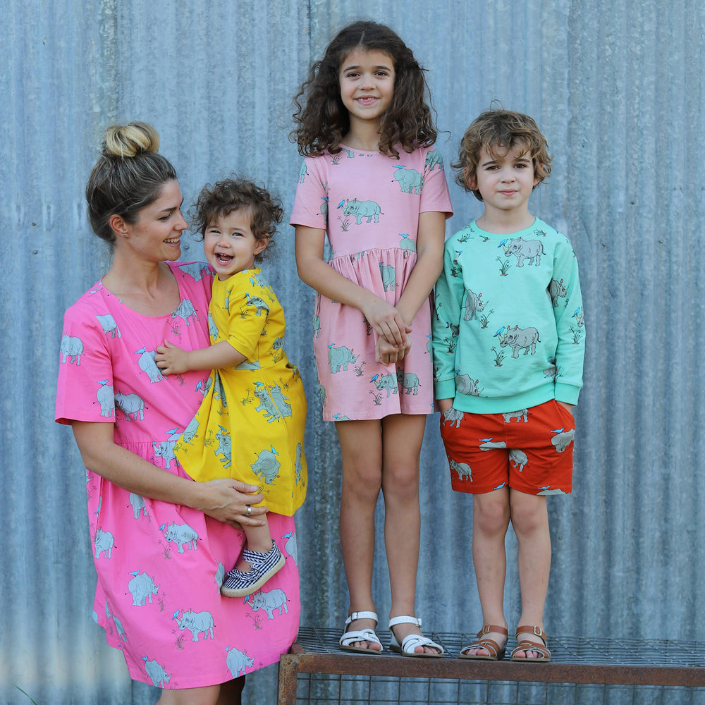 Family wearing matching scandi clothing.  Mum wears a pink lemonade coloured dress, she is holding a toddler with curly hair who is wearing a bright lemonzest yellow twirling dress.  The eldest child is wearing a dusty pink coloured a line dress and the boy on the right is wearing a biscay bay blue coloured jumper with tigerlily red shorts.  He has his hands in his pockets.  All clothing is in different colours of the same rhino print material.