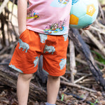 Close up of child wearing tigerlily red shorts with rhino print.  The shorts have pockets.  The child has one hand in their pocket and the other hand is clutching a soccer ball.  You can also see the bottom of the peach coloured shirt that has a duck family printed on it in a repeat pattern.