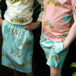 Close up of shorts with ducks.  Shorts have pockets and Childs hand is in pocket.  Child wears matching peach coloured tee with duck family print.  Girl wears matching duck jumper and matching mint coloured skirt in matching duck print.
