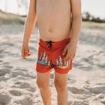 Boy at the beach wearing red meerkat swimshorts
