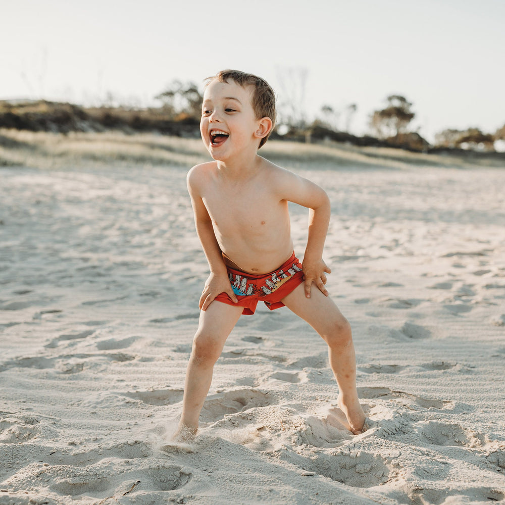 Boy at the beach laughing wearing swim shorts in a vibrant cherry red featuring a meerkat family in a repeat pattern