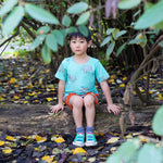 Young boy wearing bright blue t-shirt with rhino print he is sitting on a log wearing blue shoes with colourful laces