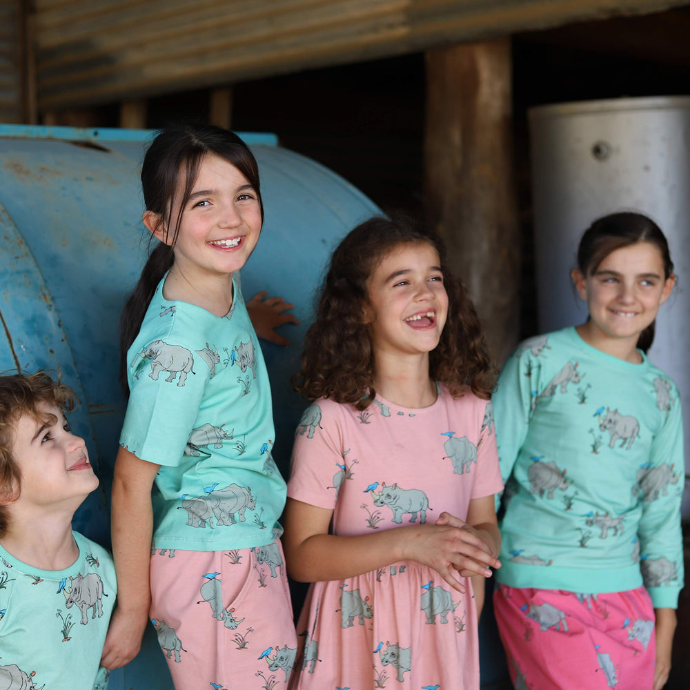Picture of 4 children wearing matching outfits in different styles.  All clothing features the same matching rhino print, the print features on a tshirt, shorts, an a-line dress, a skirt and a lightweight jumper.  The fabric colour varies from a bright biscay bay blue to a dusty pink to a vibrant pink lemonade.  All the children are smiling.  Because they know they look Oomphtastic!