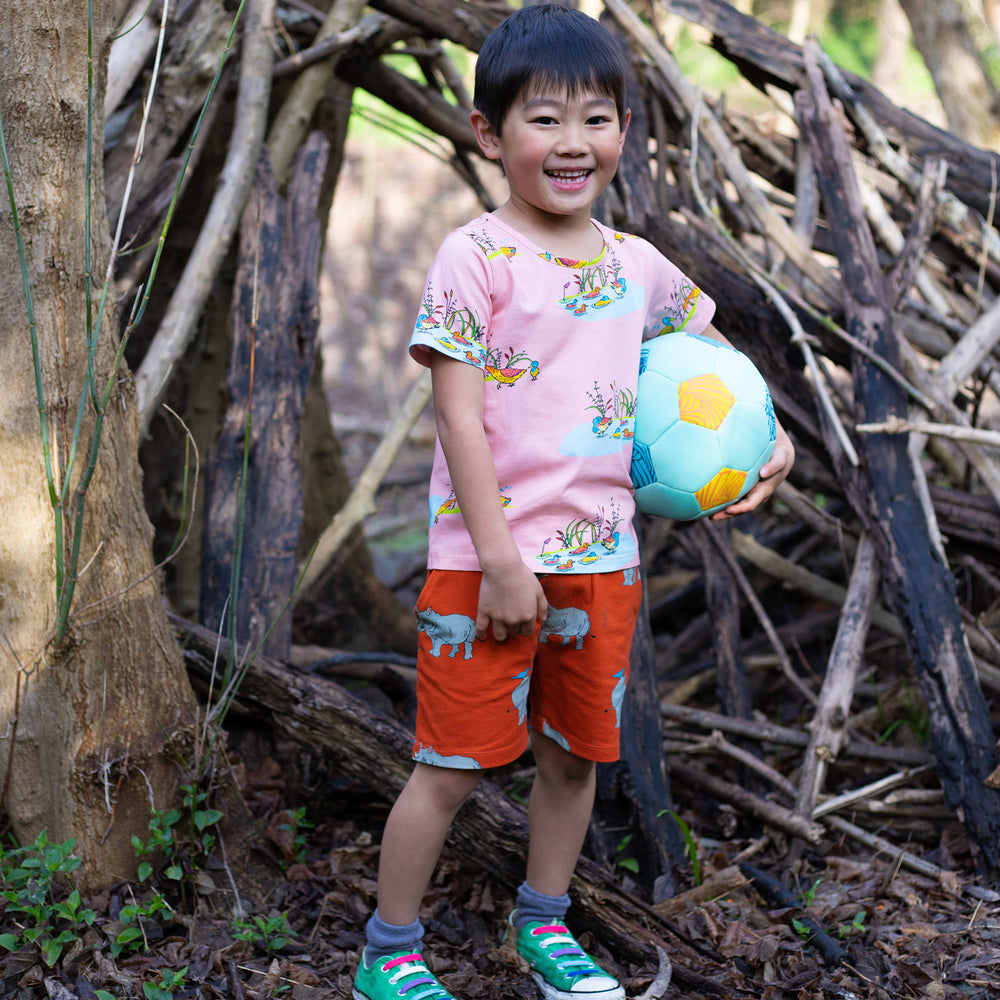 Boy wearing peach coloured duck shirt.  He is wearing red drawstring shorts with pockets that have a rhino print in a repeat pattern.   He is holding a soccer ball and wears bright aqua coloured shoes with colourful shoelaces.
