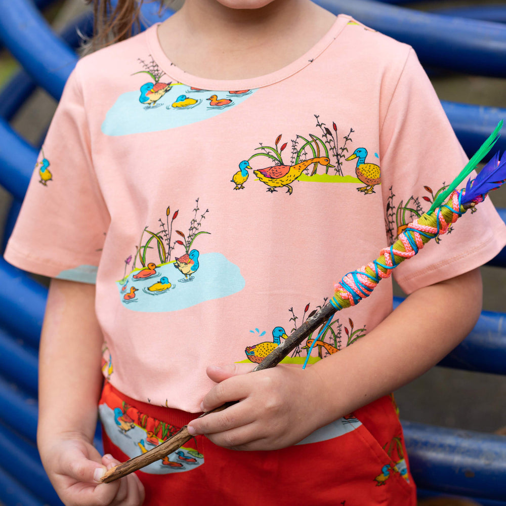 Close up of peach duck shirt showing hand-drawn illustration of duck family.  She wears matching red shorts featuring the same duck illustration. She is holding a stick hat has colourful yarn twirled around half of it.