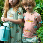 Brother and sister in matching duck print outfits.  Girl wears cool mint coloured a line dress with pockets and duck print.  She is holding a blue watering can.  Boy wears peach coloured short sleeved tee and matching cool mint coloured drawstring shorts with pockets, all clothing items feature the same duck print.