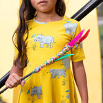 Close up of girls short sleeved skater-style twirling dress in a vibrant lemonzest colour.  The dress features a repeat pattern of a hand-drawn illustration of a grey rhinoceros with a blue tick bird balancing on it's horn and back.  The girl is holding a stick that has coloured wool and feathers entwined around it like a cross bow.