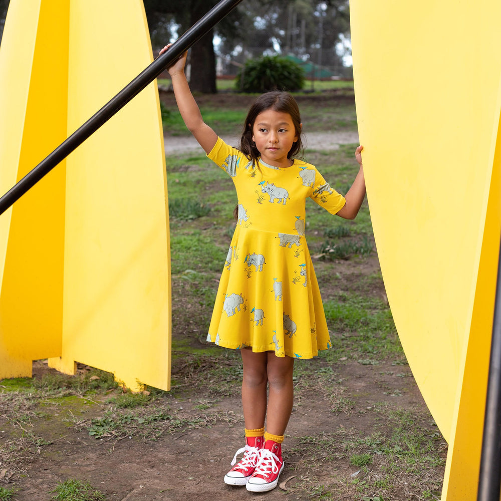 Girl wearing short sleeved skater-style twirling dress in a vibrant lemonzest colour.  The dress features a repeat pattern of a hand-drawn illustration of a grey rhinoceros with a blue tick bird balancing on it's horn and back.  The girl is holding onto a cross bar of playground equipment and wearing red converse shoes.