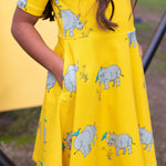 Close up photo showing deep pocket details of girls skater-style twirling dress.  The dress is a vibrant yellow lemonzest featuring a repeat pattern of grey rhinoceros with a blue tick bird balancing on its horn and back