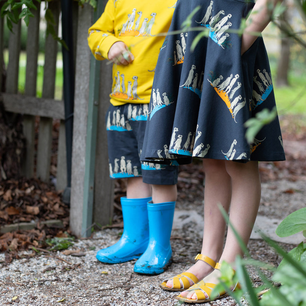 Brother and sister wearing scandi-style clothing in matching print.  Boy wears bright yellow jumper with meerkat print and matching carbon coloured meerkat shorts.  Girl has hands in pockets and wears matching carbon coloured twirl dress with meerkats