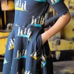 Close up image of girl wearing skater-style twirl dress with hands in pockets.  Dress has a meerkat print in repeat pattern printed on dark carbon coloured organic fabric