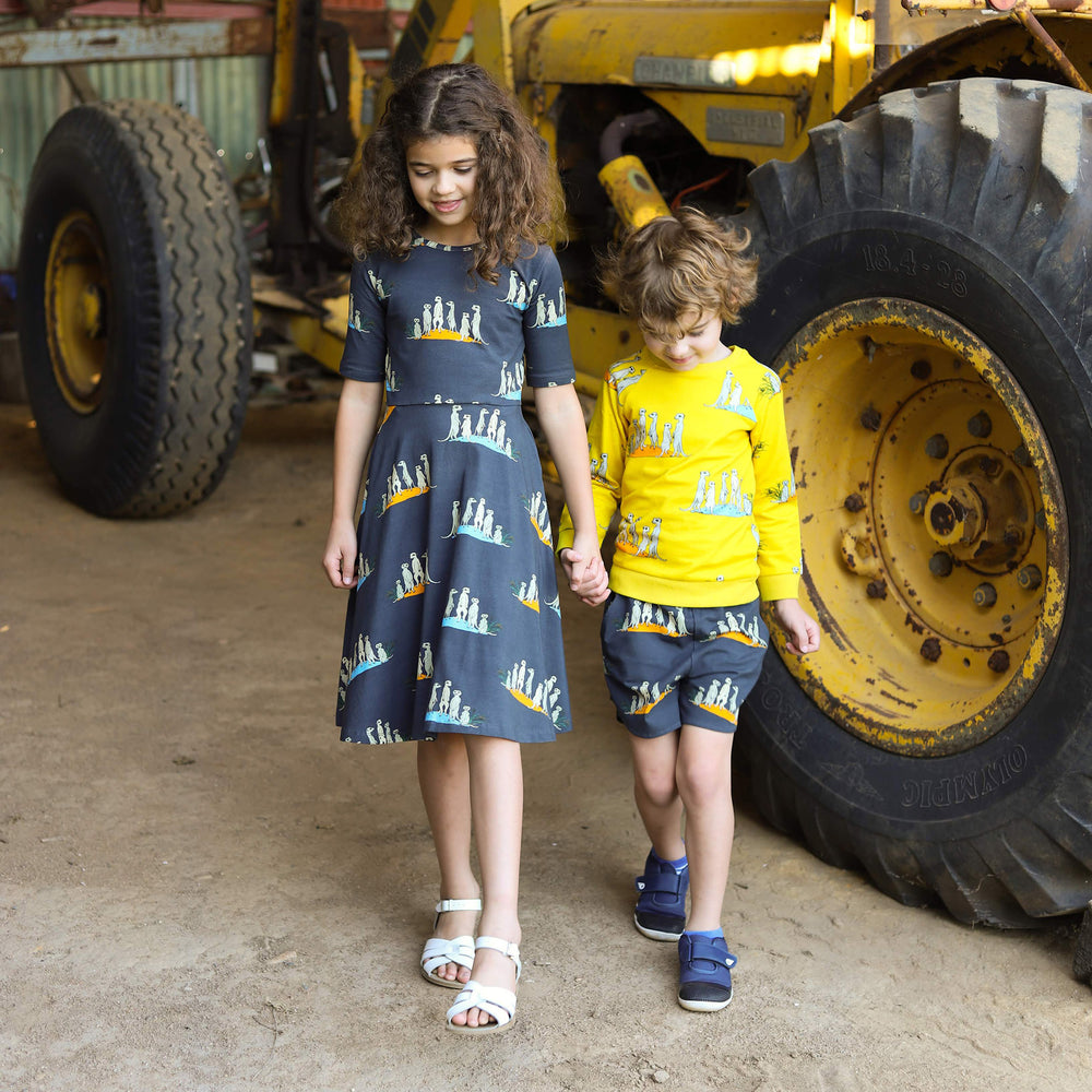 Siblings wearing matching scandi style outfits with meerkat print.  Oomph and Floss meerkat dress in dark charcoal colour.  Boy wears yellow meerkat jumper and grey kids shorts with meerkats.