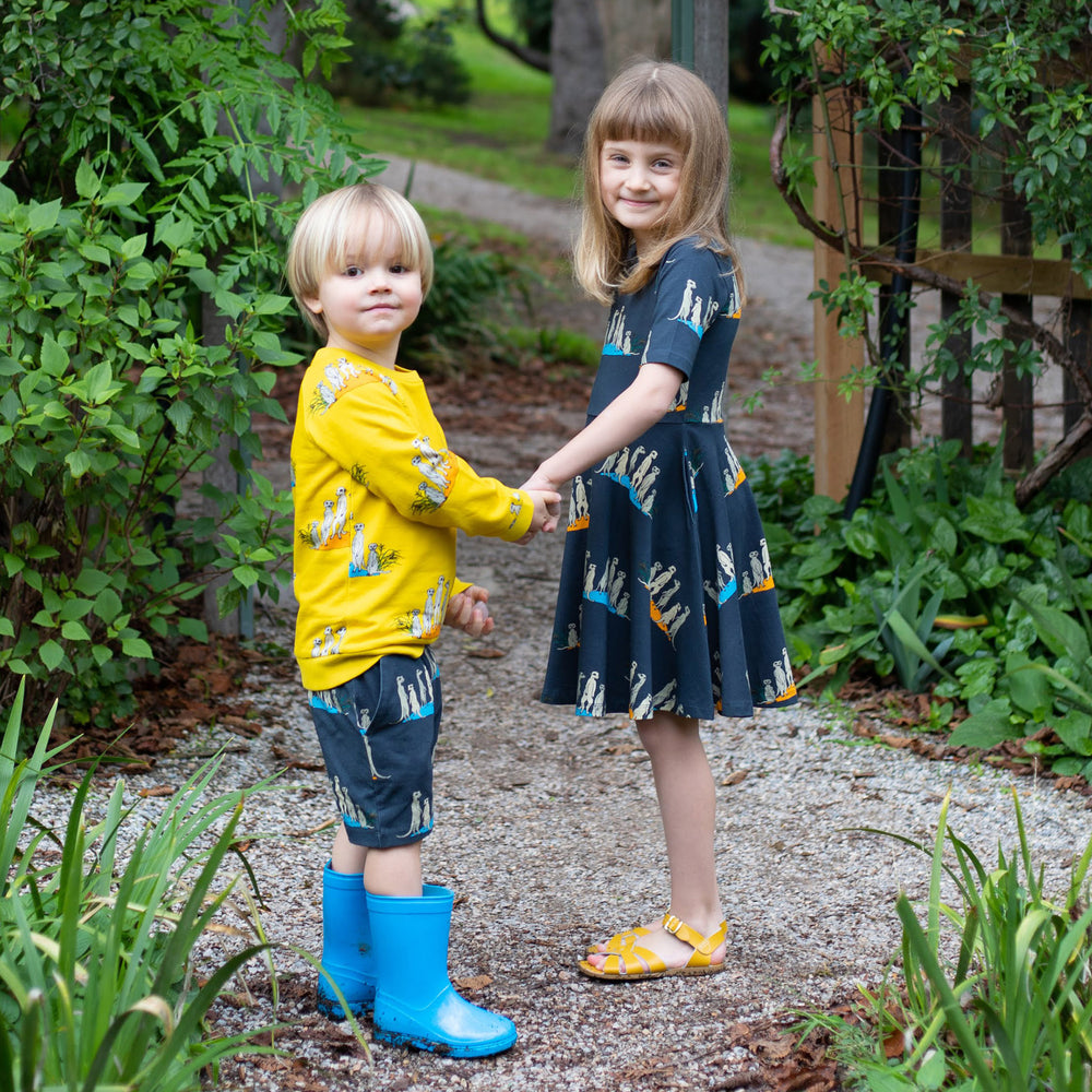 Kids in matching meerkat outfits.  Boy wears yellow kids meerkat top and matching kids meerkat drawstring shorts girl wears meerkat dress with pockets and twirl factor