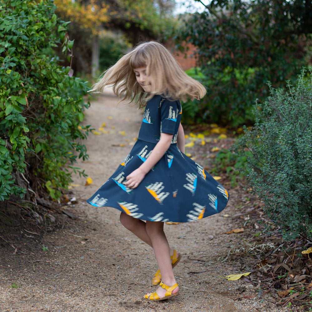 Girl twirling in meerkat dress.  Dark grey girls dress with meerkat family print