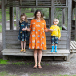 Family wearing matching scandi-style clothing.  Mum wears scandi style orange babydoll dress with meerkats.  Girl wears dark grey twirling dress with meerkats.  Boy wears matching dark grey shorts with meerkats and bright yellow meerkat top