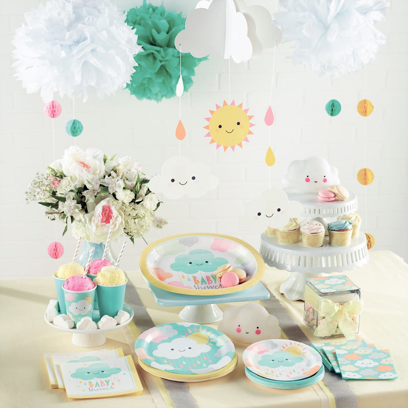 baby shower party range in unisex pastel colours laid out on a table. Decorated with clouds, raindrops and sunshine