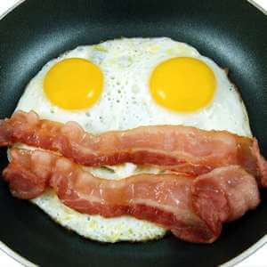 eggs and bacon frying in a pan