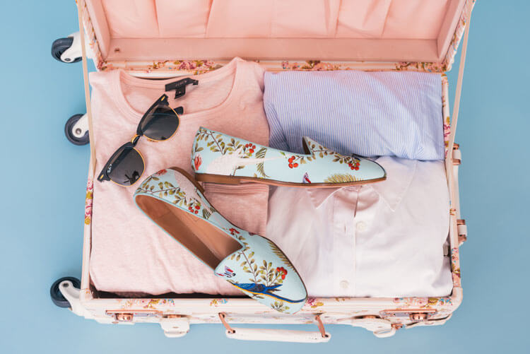 open suitcase with sunglasses and shoes
