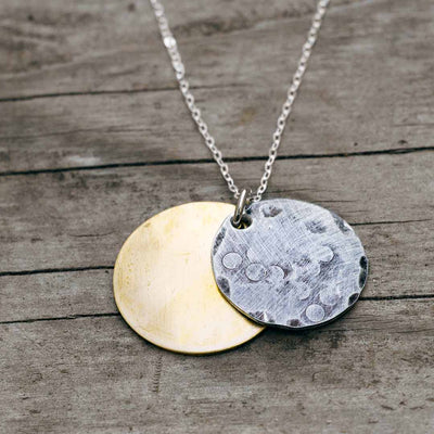 Solar eclipse necklace, science jewelry for astronomers, teachers, students, and astronomy enthusiasts. Made from an antiqued silver aluminum disc over a weathered brass disc.