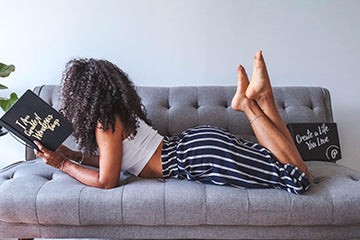 Black woman reading and journaling on grey couch