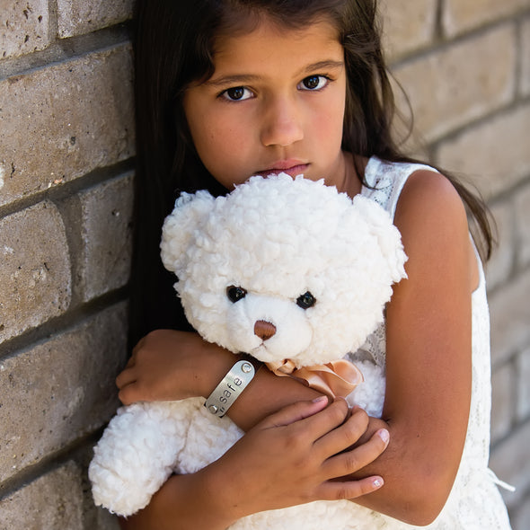 girl holding bear wearing safe band