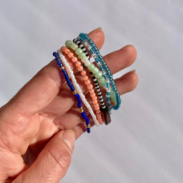 hand with beaded survivor band bracelets