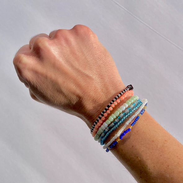 wrist with beaded survivor band bracelets